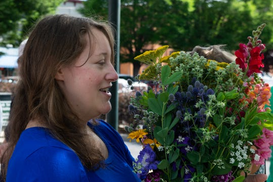 Annie Bellinger walks away from Susan Roepke's stand on Saturday at the Staunton Farmers Market with a bouquet of flowers to take to a masquerade ball her family was hosting. Bellinger said her daughters and the other children who would be attending were excited for the big day.