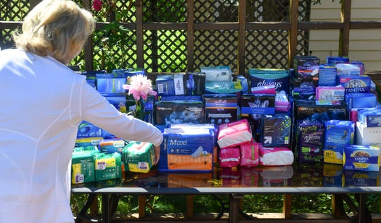 Donated sanitary products are collected on a table in the backyard of Bobbi Murphy's home during a party Saturday, June 22, in St. Cloud. Murphy was inspired to organize the fundraising effort after reading about the need for products among homeless people.