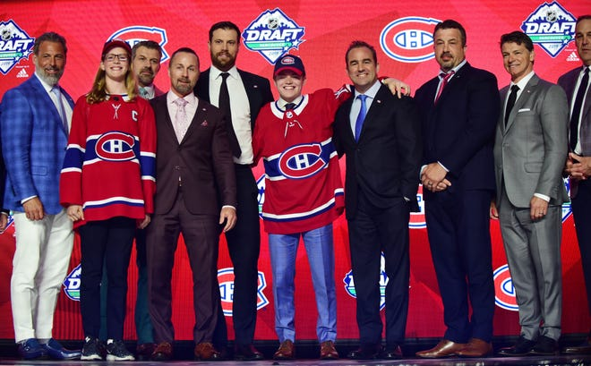 Cole Caufield, center, a former Stevens Point Area Senior High star, poses after being selected 15th overall by the Montreal Canadiens in the first round of the NHL Draft on Friday.