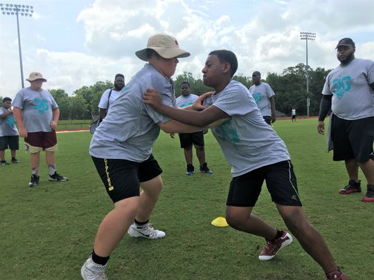 Wyatt Crosby, 13, (left) goes one-on-one with Josiah Houston, 13, during Ronnie Harrison's football camp at Florida High School.