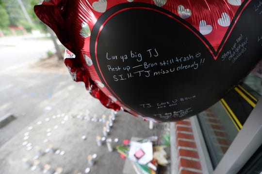 A balloon with handwritten notes on it floats above a  memorial set up outside Clippers on South Adams Street honoring Tyras McKinney, a barber who was shot and killed after a dispute in the shop last Thursday. A note on the door says the shop would reopen Monday, June 24, 2019.