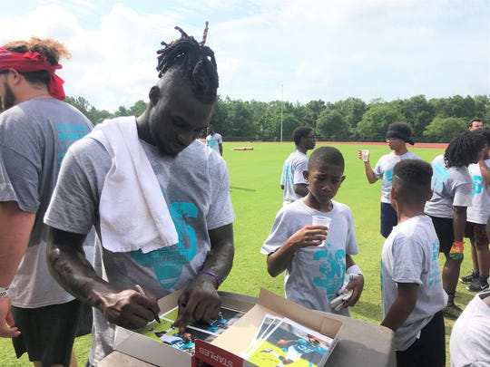 Jacksonville Jaguars safety Ronnie Harrison signs autographs for kids attending his football camp at Florida High School on Saturday, June 22, 2019.