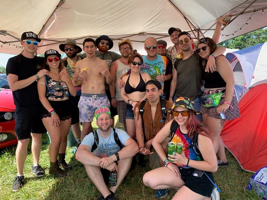 Evan Kelly (far left) and Gillian Rizza (second from the left) pose for a photo with friends and family after the couple got engaged at the campground Friday at Firefly Music Festival in Dover.