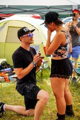Evan Kelly (left) asks Gillian Rizza (right) to marry him Friday in the campgrounds at Firefly Music Festival in Dover.