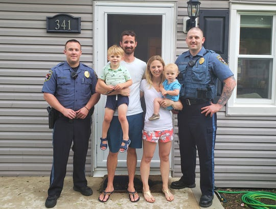 Brick police Officers Tyler Stephenson, left, and Kevin Docherty, right, reunite with the Travers family after saving the life of 21-month-old Bruce, who is being held by his mother, Melissa Travers. Ryan Travers is holding the couple's 3-year-old son, Will.