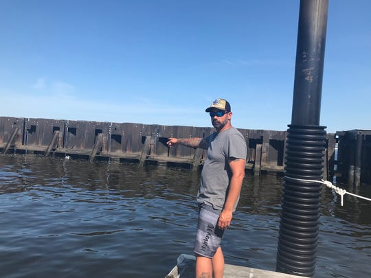 Scott Policastro, captain of Jenna P Sportfishing, points to where a minke whale became wedged in a dock at Sandy Hook Bay Marina and died.