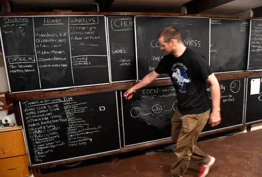 Sean Grose shows some of the custom sliding chalkboards installed in his office at Waverly's Coffee & Gifts on June 14. While he embraces technology, Grose opined that the tactile nature of the chalkboards was a boon to creativity for himself and the couple's daughter, Ilya.
