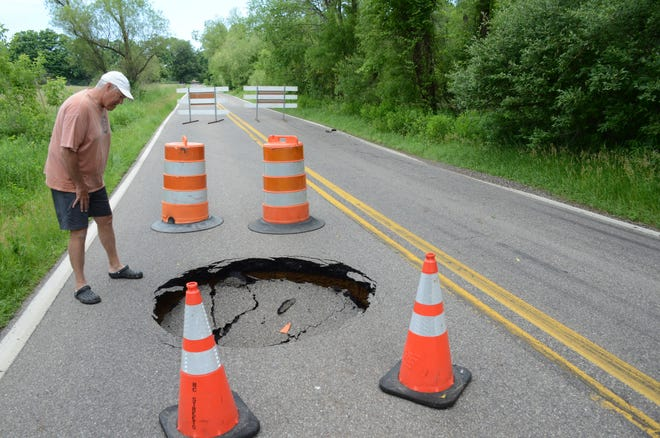 Jeff Smith, who lives in nearby Minges Hills on Battle Creek's south side inspects a sink hole Sunday on South Helmer Road.