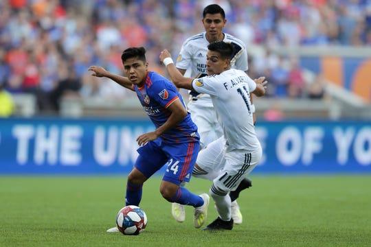FC Cincinnati midfielder Frankie Amaya (24) and Los Angeles Galaxy forward Favio Alvarez (11) battle for possession in the first half of an MLS soccer game, Saturday, June 22, 2019, at Nippert Stadium in Cincinnati.