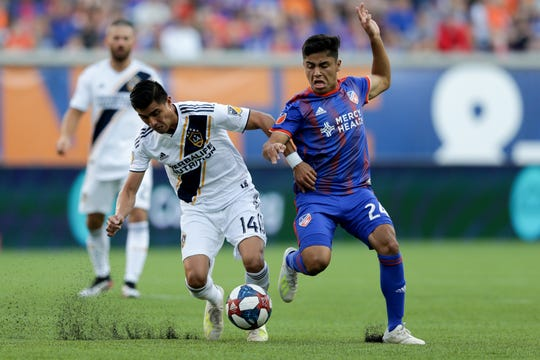 Los Angeles Galaxy midfielder Joe Corona (14) and FC Cincinnati midfielder Frankie Amaya (24) battle for possession in the first half of an MLS soccer game, Saturday, June 22, 2019, at Nippert Stadium in Cincinnati.