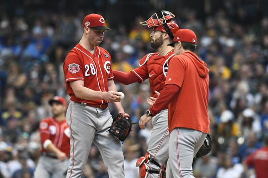 Jun 23, 2019; Milwaukee, WI, USA; Cincinnati Reds starting pitcher Anthony DeSclafani (28) hands the ball to Cincinnati Reds manager David Bell (25) as he comes out of the game in the fifth inning agains the Milwaukee Brewers at Miller Park. Mandatory Credit: Michael McLoone-USA TODAY Sports