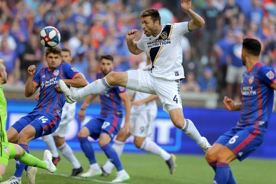 Los Angeles Galaxy defender Dave Romney (4) take a shot on goal in the first half of an MLS soccer game against FC Cincinnati, Saturday, June 22, 2019, at Nippert Stadium in Cincinnati.