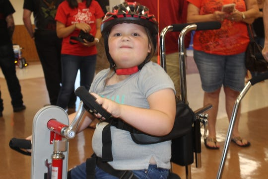 5-year old Kalynn Turnbow smiles as volunteers watch her ride her new adaptive tricycle on June 22, 2019.