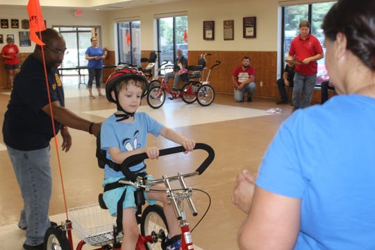 6-year old Judah McMahan gets some encouragement riding his new adaptive tricycle on June 22, 2019.