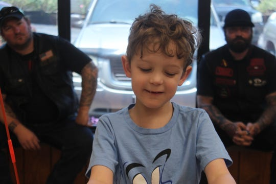 6-year old Judah McMahan gets ready to try out his new adaptive tricycle as some bikers look on on June 22, 2019.