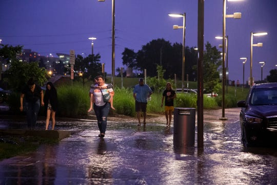 People leaving the Shawn Mendes concert navigate through flood waters along Robert D. Ray Drive after flash floods swept through the area on Saturday, June 22, 2019, in Des Moines.