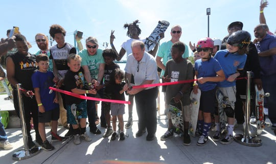 Mayor Mike Duggan gets help from young skate boarders cutting the ribbon for the new skate park in Riverside Park in Detroit Mich.Saturday, June 22, 2019.