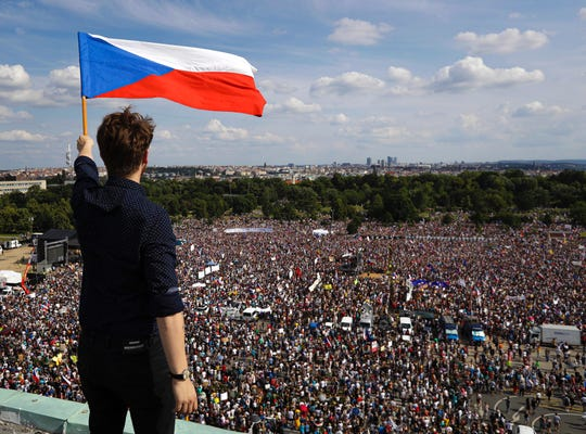 A man waves the Czech flag as people protest in Prague, Czech Republic, Sunday.