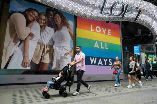 In this Thursday, June 20, 2019, people walk past a pride display at the Loft store in New York's Times Square.