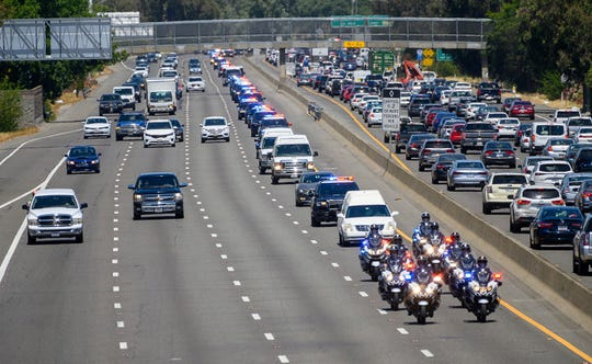 A funeral hearst is led by an honor procession for Sacramento police officer Tara O'Sullivan as they drives along Highway 99 on the outskirts of Sacramento, on its way to the funeral home in Elk Grove, Calif. on Friday, June 21, 2019.