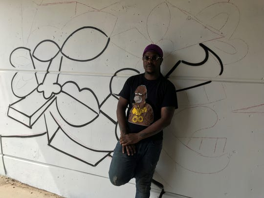 Artist Sheefy McFly poses with his unfinished mural, at East Seven Mile near John R.