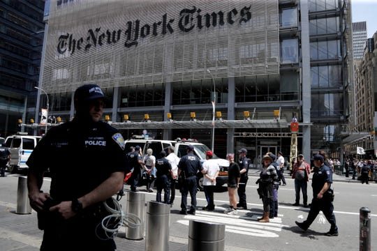 New York Police officers take into custody activists during a climate change rally outside of the New York Times building, Saturday, June 22, 2019, in New York.