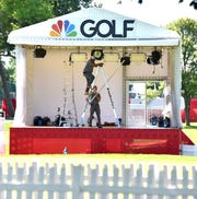 Golf Channel lighting technicians Rasheen Crawley, left, and Tim Juengel set up studio lighting for the Rocket Mortgage Classic.