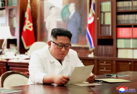 In this undated photo provided on Sunday, June 23, 2019, by the North Korean government, North Korean leader Kim Jong Un reads a letter from U.S. President Donald Trump.
