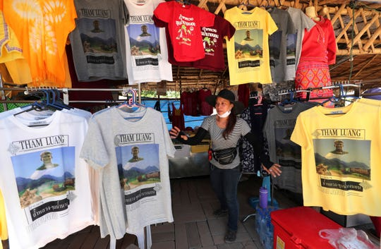 In this Saturday, June 22, 2019, photo, a T-shirt vendor waits for customers near the Tham Luang Nang Non cave in Mae Sai, Chiang Rai province, northern Thailand.