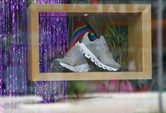 This Thursday, June 20, 2019, photo shows running shoes on display with a rainbow flag at Red Coyote Running and Fitness in Oklahoma City, to celebrate Pride Month.