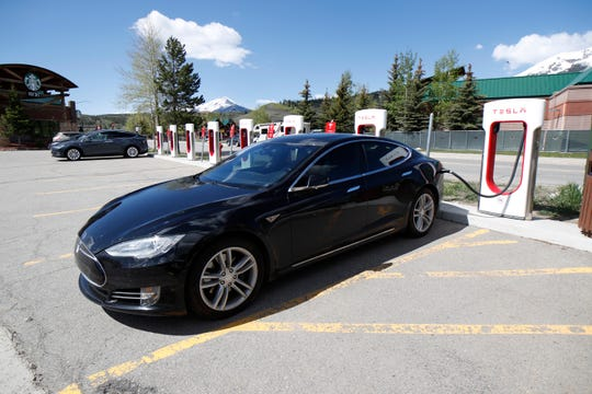 In this Saturday, June 8, 2019, photograph, a Model S sedan charges at a Tesla supercharging station in Silverthorne, Colo.