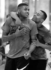 Jaidon Hunter, left, is congratulated by teammate Trayvon Jones after sinking a three-pointer to force overtime in their first bracket game of the Dust Bowl at the C.K. Newsome Community Center Thursday evening.