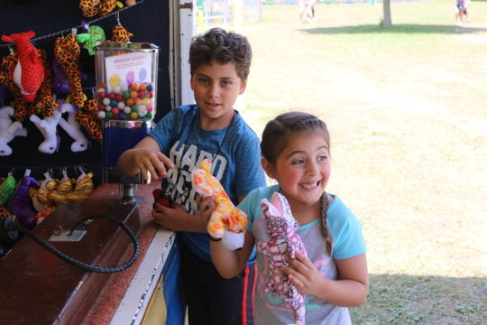 Steeven and Briella Escobar, of Woodville, pick out some prizes after playing a carnival game at the Gibsonburg Homecoming Festival on Saturday.