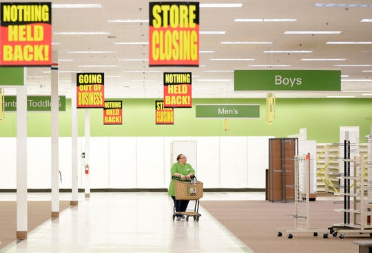 Shopko employee Amy Klaus pushes a shopping cart through the nearly empty Mason Street store in Green Bay on June 23, the Ashwaubenon-based company's last day of business.