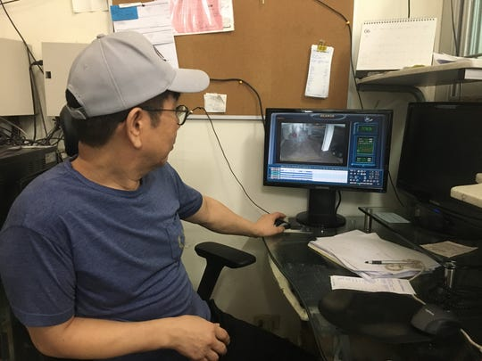Ikjin Yoon, San Jose Supermarket general manager, watches security footage of the armed robbery that occurred at the market early Sunday morning.