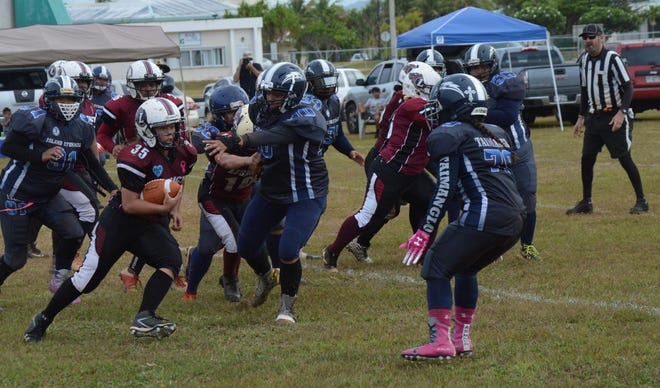 Jalana Garcia pounds away at the Island Stunnerz defense, leading her team to a 26-22 win in the title game of the Bud Light Guam Women's Tackle Football League Saturday at the University of Guam.