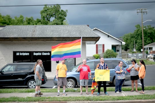 Chad Beanblossom waves a Pride flag as fellow members of the LGBTQ community stand outside of All Scripture Baptist Church in Knoxville, Tennessee, on Sunday, June 23, 2019. The church's pastor, Grayson Fritts, came under fire for preaching that the government should arrest and execute LGBTQ community members.