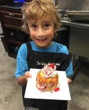 This little one looks pleased with the dessert he made during a parent/child class at the Cutting Edge Classroom, 817 North Herron Road in Farragut. June 2019