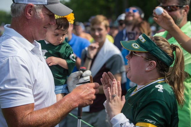 Hannah Lopez talks to Brett Favre as he holds her daughter Charleigh (15 months) during the AmFam Champ Celebrity Foursome at University Ridge Golf Course on Saturday.