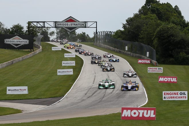 Alexander Rossi (right) finishes his pass of Colton Herta for the lead on the first lap of the REV Group Grand Prix as the field heads down into Road America's Turn 3.