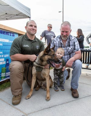 Two-year-old Gabriel Michalak and his dad, John, of Oconomowoc pause to meet Waukesha County Sheriff's K-9 Deputy Justice and his partner Deputy Kurt Thompson during a special meet and greet event at Oconomowoc City Beach on Friday, June 21, 2019. Justice was injured during an hourslong standoff in the Village of Summit earlier in the month.
