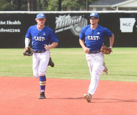 Mountain Home outfielders Luke Dibble (left) and Asa Smith run off the field after Smith hauled in a fly ball to end an inning on Friday during the AHSCA All-Star games in Conway.