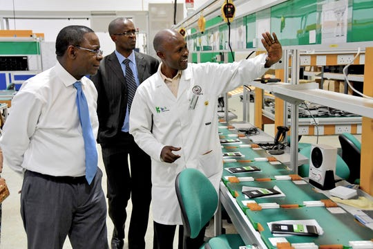 Faculty members from Moi University give MTSU President Sidney A. McPhee, left, a tour of a digital assembly plant that the Kenyan institution operates.