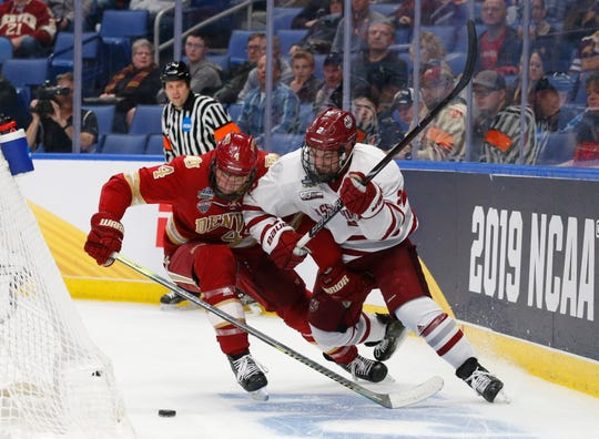 Massachusetts defenseman Marc Del Gaizo (2) and Denver defenseman Griffin Mendel (4) race to the puck behind the net during the third period in a semifinal of the Frozen Four on April 11, 2019, in Buffalo, N.Y.