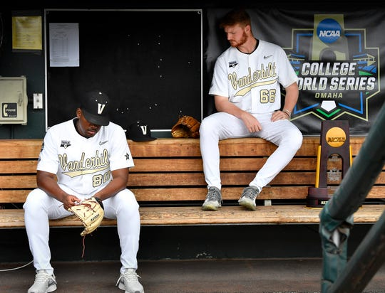 Vanderbilt pitchers Kumar Rocker (80) and Drake Fellows (66) relax in the dugout before a photo session Sunday at TD Ameritrade Park in Omaha, Neb.