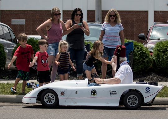 A Shriner high fives kids watching the parade Saturday celebrating the final weekend of the Licking County Shrine Tournament's 75th year.