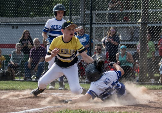 Cole Smith of MedBen slides safely into home plate as Max Frost of Park National Bank tries to tag him out Saturday in the Varsity semifinals of the Licking County Shrine Tournament. PNB won 12-7 and will play Edward Jones for the title on Thursday at Mound City.