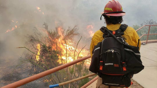 A firefighter stares at the Woodbury Fire in the Superstition Wilderness.