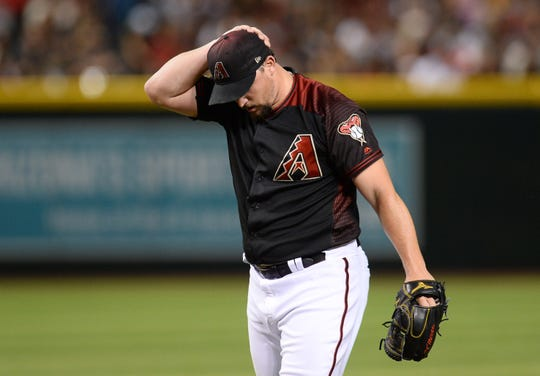 Jun 22, 2019; Phoenix, AZ, USA; Arizona Diamondbacks starting pitcher Zack Godley (52) reacts against the San Francisco Giants during the third inning at Chase Field. Mandatory Credit: Joe Camporeale-USA TODAY Sports