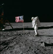 "Astronaut Edwin E. ""Buzz"" Aldrin Jr. poses for a photograph beside the United States flag during the Apollo 11 moon walk on July 20, 1969."